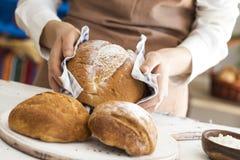 Żeńska ręka trzyma gorącego świeżo piec chleb Obraz Stock