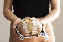 Żeńska ręka trzyma gorącego świeżo piec chleb Zdjęcia Royalty Free