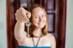 Żeńska ręka trzyma klucz dom na tle drewniany drzwi Posiadać nieruchomości pojęcie Fotografia Royalty Free
