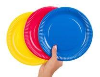 Żeńska ręka trzyma kolorowych rozporządzalnych talerze odizolowywający na bielu Obraz Royalty Free