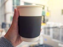 Żeńska ręka trzyma papierową filiżankę gorąca kawa, selekcyjna ostrość Fotografia Royalty Free