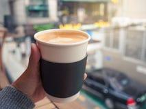 Żeńska ręka trzyma papierową filiżankę gorąca kawa, selekcyjna ostrość Zdjęcia Royalty Free