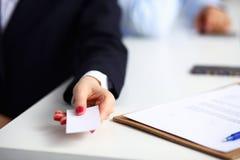 Żeńska ręka trzyma pustego wizytówki obsiadanie na biurku, selekcyjna ostrość fotografia royalty free