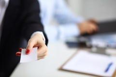 Żeńska ręka trzyma pustego wizytówki obsiadanie na biurku, selekcyjna ostrość zdjęcie stock
