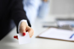 Żeńska ręka trzyma pustego wizytówki obsiadanie na biurku, selekcyjna ostrość obrazy royalty free
