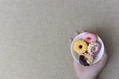 Żeńska ręka trzyma smakowitego pączek na tkaniny tle Zdjęcie Royalty Free
