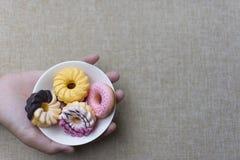 Żeńska ręka trzyma smakowitego pączek na tle Fotografia Stock