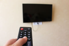 Żeńska ręka trzyma TV daleki Obrazy Royalty Free