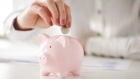 Żeńska ręka wkłada euro pieniądze w prosiątko banka zbiory wideo