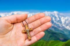 Żeńska ręka z drewnianym krzyżem na góry tle Zdjęcia Royalty Free