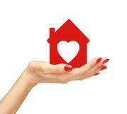 Żeńska ręka z małym modelem odizolowywającym na bielu dom Obraz Royalty Free