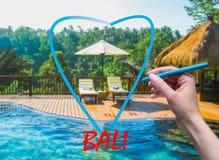 Żeńska ręka z pióra rysunkowym sercem i Bali tłem Obrazy Royalty Free