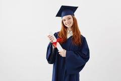 Żeńska rudzielec magistrant/magistrantka z dyplomem ono uśmiecha się patrzejący kamerę Copyspace Obrazy Stock