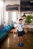 Żeńska terapeuta mienia chłopiec pozycja na błękitnej stres piłce obraz stock