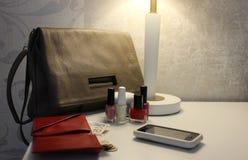 Żeńska torba, otwarty portfel z, pieniądze, smartphone i gwoździa połyskiem na strona stole, Obrazy Royalty Free