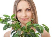 Żeńska twarz za uśmiechu ulistnienia rośliną zdjęcia royalty free