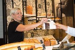 Żeńska wlaściciel sklepu porci kanapka męski klient w piekarni Obrazy Royalty Free
