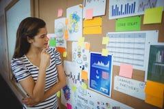 Żeńska wykonawcza patrzeje tablica informacyjna obrazy stock
