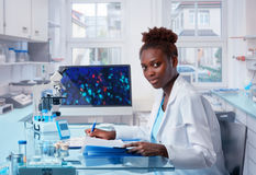Żeński Afrykański naukowiec pracuje w nowożytnym biologicznym laboratorium fotografia stock