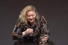 Żeński alkoholizm Kobieta starzał się jeden pije ajerówkę od butelki i zdjęcie royalty free
