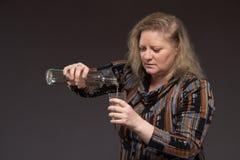 Żeński alkoholizm Kobieta starzał się jeden pije ajerówkę od butelki i zdjęcie stock