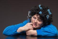 Żeński alkoholizm Kobieta w bathrobe i curlers z blac obraz stock