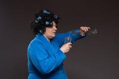 Żeński alkoholizm Kobieta w bathrobe jeden i curlers pije obrazy royalty free