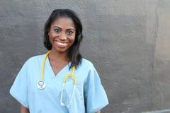 Żeński amerykanin afrykańskiego pochodzenia pielęgniarki lub lekarki ono uśmiecha się odizolowywam nad ciemnym tłem Obraz Royalty Free