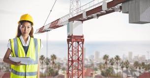 Żeński architekt trzyma błękitnych druki podczas gdy stojący żurawiem zdjęcie stock