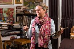 Żeński artysta patrzeje jej obrazek w jej galerii Obrazy Stock