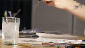 Żeński artysta trzyma farby muśnięcie, zamaczający wewnątrz barwić i nawadniać zbiory