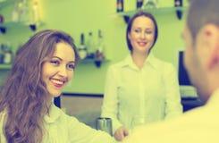 Żeński barista i dwa klienta w kawiarni Obrazy Stock