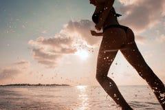 Żeński biegacz na plaży przy zmierzch sylwetką w lotniczy dalekim Obrazy Royalty Free