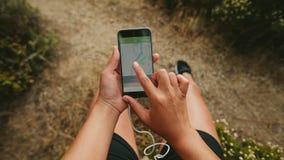 Żeński biegacz używa sprawność fizyczną app na jej telefonie komórkowym fotografia royalty free