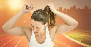 Żeński biegacz wiąże w górę włosy na śladzie przeciw pomarańcze migocze przeciw linii horyzontu Obraz Stock
