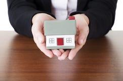 Żeński bizneswoman wręcza mienie dom. Obrazy Stock
