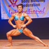 Żeński bodybuilder napina jej mięśnie pokazywać ona budowę ciała Fotografia Stock