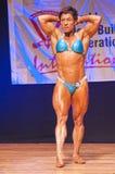 Żeński bodybuilder napina jej mięśnie pokazywać ona budowę ciała Obrazy Royalty Free