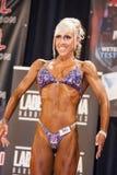 Żeński bodybuilder pokazuje jej najlepszy frontową pozę na scenie Fotografia Stock