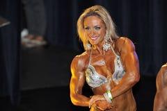 Żeński bodybuilding konkursant pokazuje jej klatki piersiowej pozę Zdjęcia Stock