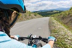 Żeński cyklista jedzie jej rower na drodze Zdjęcia Royalty Free