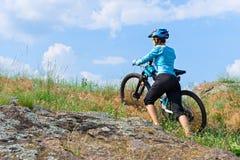 Żeński cyklista z jej roweru górskiego wspinaczkowy up skała na stopie Zdjęcia Stock
