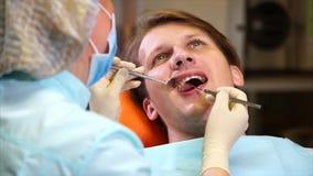 Żeński dentysta egzamininuje oralnego zagłębienie pacjent z stomatologicznym lustrem zbiory wideo