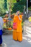 Żeński Europejski pojawienie Hindus trzyma smartphone Ashram, Włochy Sierpień 29, 2016 Obrazy Royalty Free