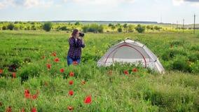 Żeński fotograf na kwiatu pola podróży pobliskim namiocie zdjęcie wideo