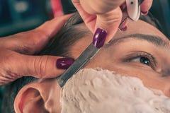 Żeński fryzjer męski goli klienta zdjęcie stock