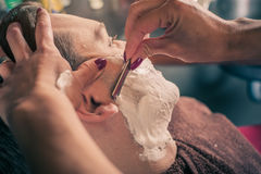 Żeński fryzjer męski goli klienta zdjęcie royalty free