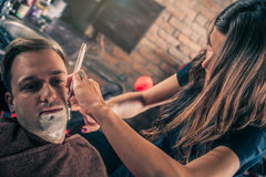 Żeński fryzjer męski goli klienta obraz stock