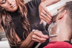 Żeński fryzjer męski goli klienta obraz royalty free