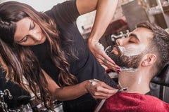 Żeński fryzjer męski goli klienta obrazy stock